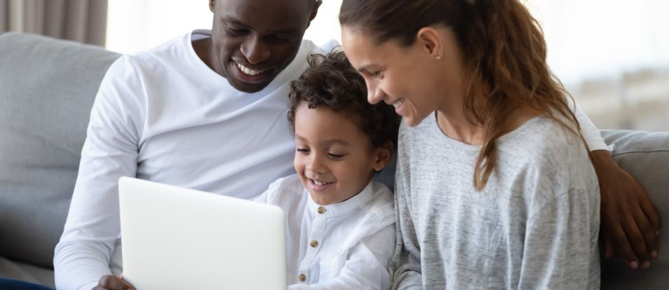 Glad familj av som sitter tillsammans pa en bekvam soffa i vardagsrummet och haller i barbar dator