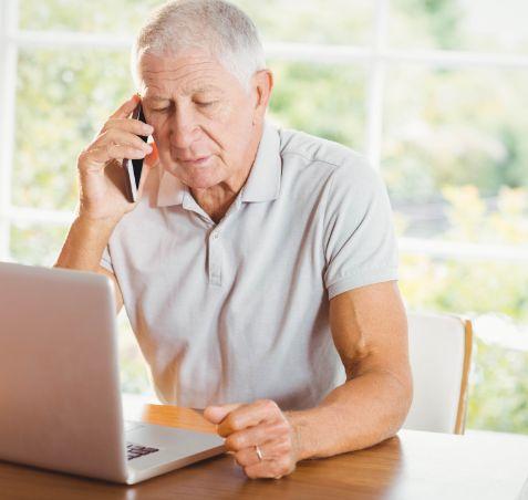 Koncentrerad aldre man som ar hemma sitter vid sin barbara dator och pratar i telefon